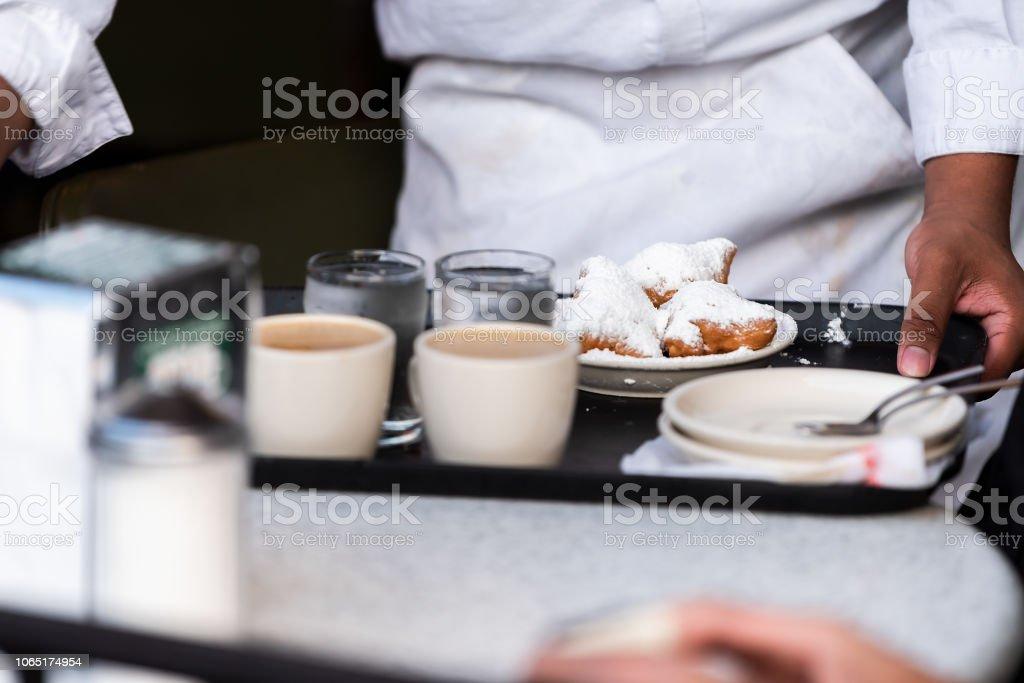 Nova Orleans, EUA famoso café restaurante na velha cidade de Louisiana, com garçom, colocando a bandeja na mesa com donut de tostas pastelaria popular - foto de acervo