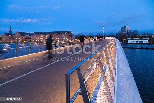 New pedestrian and bicycle bridge Lille Langebro with silhouette of cyclist in Copenhagen, Denmark. Evening city skyline