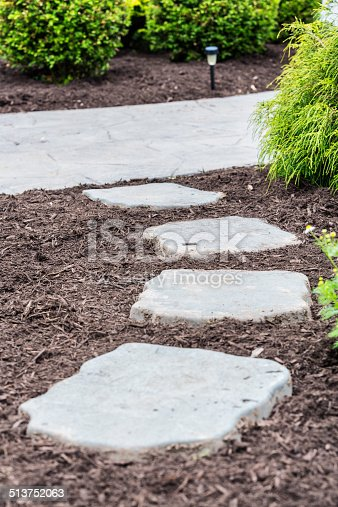 A landscape service worker has just  finished spreading a fresh new layer of shredded pine bark garden mulch around this suburban home's flagstone footpath and poured concrete walkway.