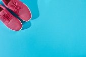 New pink sneakers on blue background with copy space. Sport concept. Active lifestyle, body care concept. Top view. Copy space. Flat lay. Still life