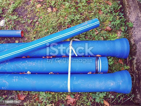 New blue pipes or tubes. Fluid conveyance. Pipeline construction. Pipes fastened with plastic tape