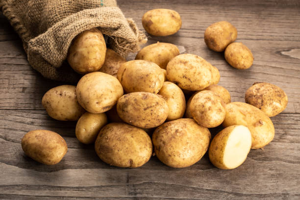 New potatoes on wooden background. stock photo