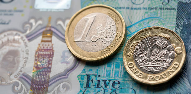 New Pound Coin and Euro New UK pound coin with a euro coin placed on top of the new five pound note. british currency stock pictures, royalty-free photos & images