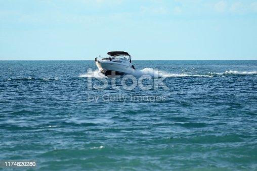 new powerboat speeding towards camera with blue sky