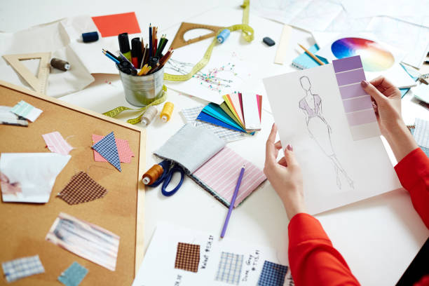 New pret-a-porter trend Designer of fashionable clothes holding paper with sketch of new dress and swatch of lilac hints fashion designer stock pictures, royalty-free photos & images
