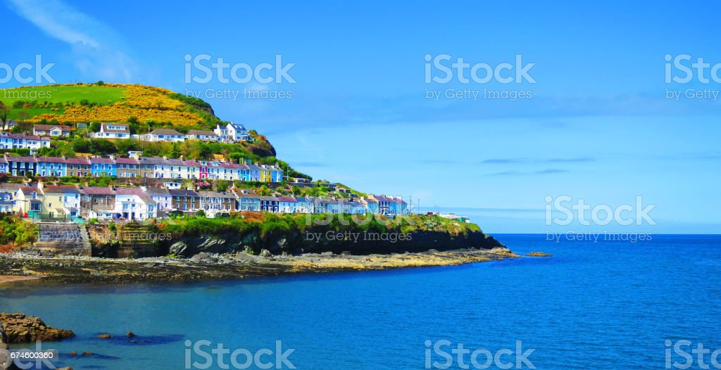 New Quay - 'Cei Newydd', picturesque houses, pubs and restaurants cling to the hills rising above the blue waters of Cardigan Bay - West Wales coast holiday resort for sailing, fishing, water sports stock photo