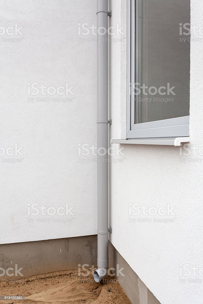 New rain gutter on a white wall with window stock photo
