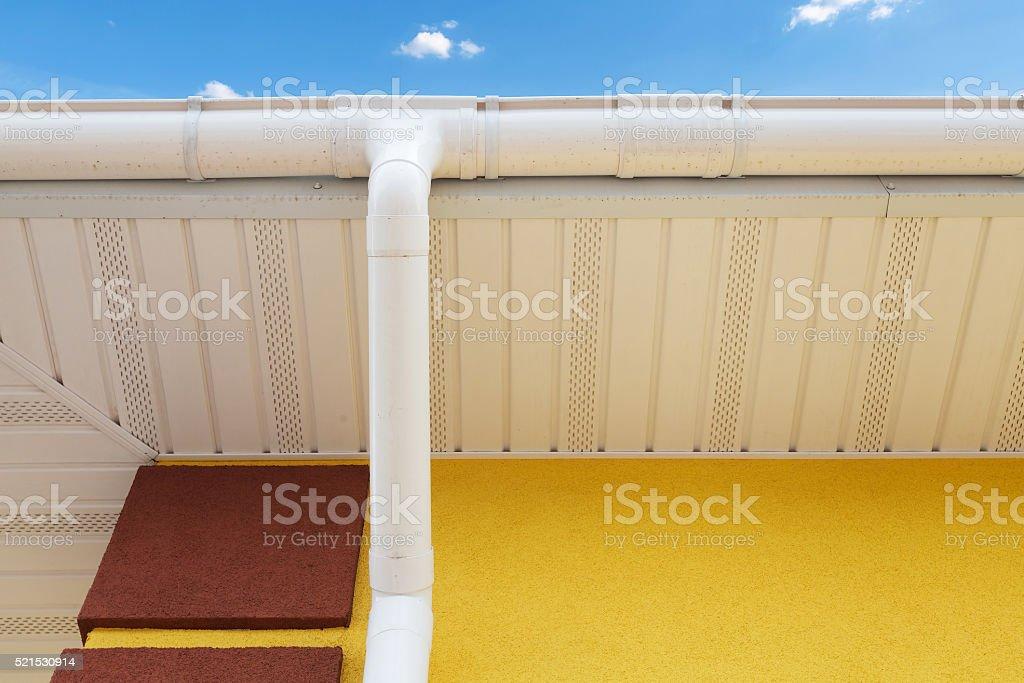 New rain gutter on yellow wall stock photo