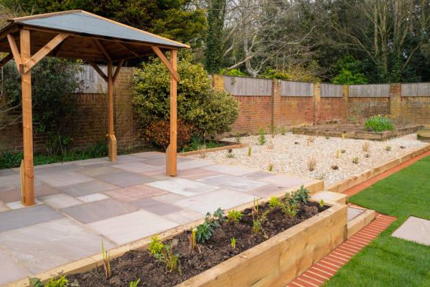 Eine neue erhöhte Terrasse mit einem hölzernen Pavillon vor einem erhöhten Blumenbeet und einem Kiesgartenbereich. – Foto