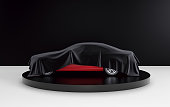 istock New red car hidden under black cover on black and white background. 3d render 924325636