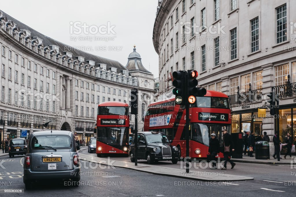 New red double-decker buses and black cabs waiting on a traffic light on Regent Street, London, UK. stock photo