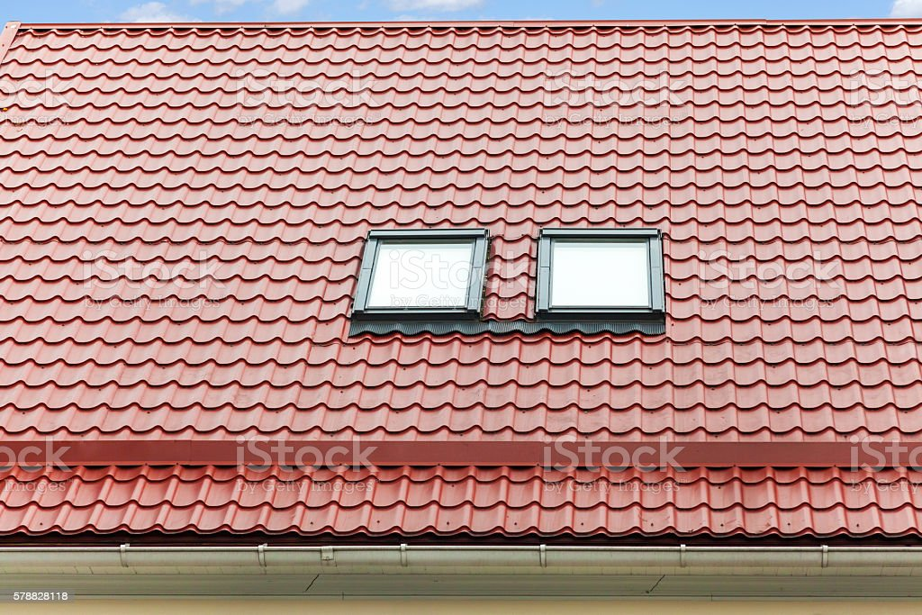 New red metal roof with skylights and rain gutter stock photo