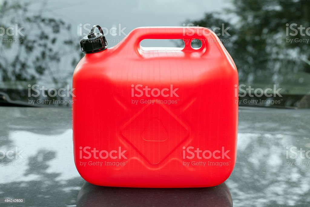 New red plastic jerrycan stands on car hood stock photo