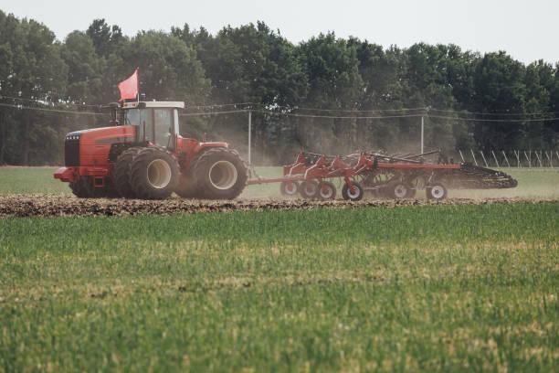 neuer roter Traktor mit großen Rädern im Feld während der Tests während der Ausstellung in Russland – Foto