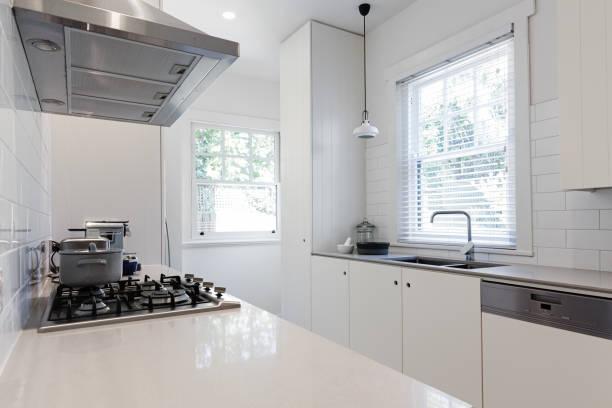 new renovated crisp white galley style kitchen - laminatschränke stock-fotos und bilder