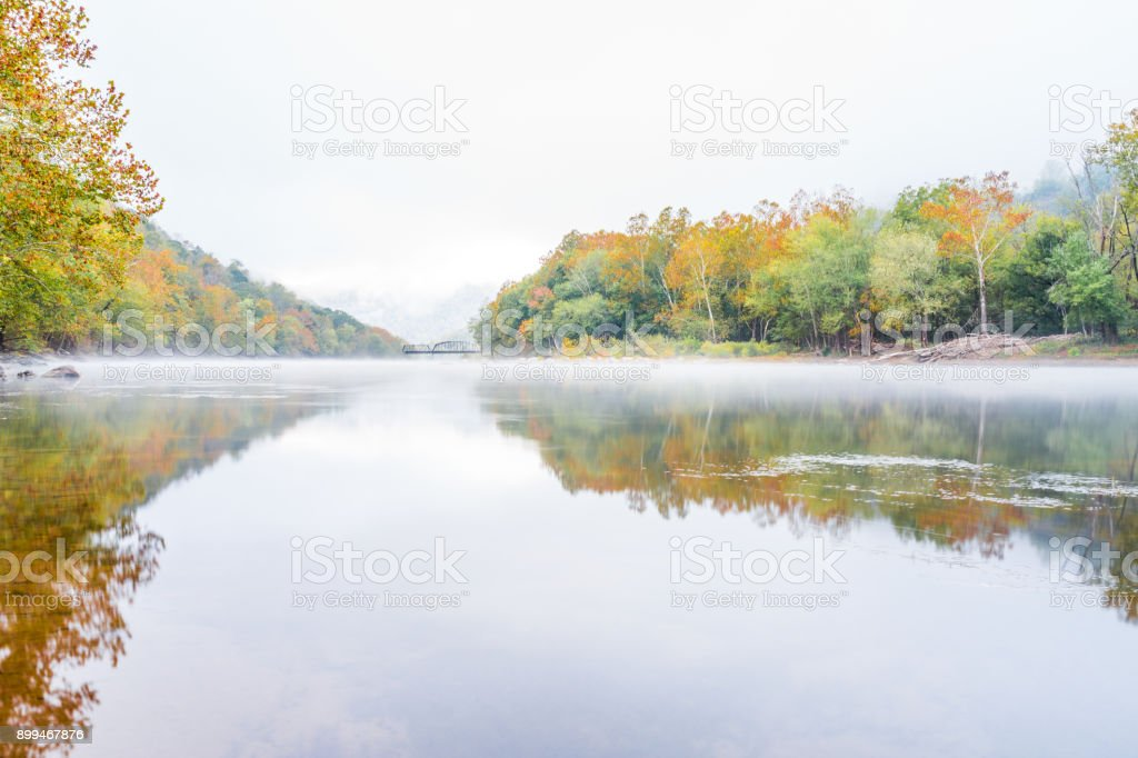 New River Gorge wide canyon water river lake during autumn golden orange foliage in fall by Grandview with peaceful calm tranquil morning bright mist fog stock photo