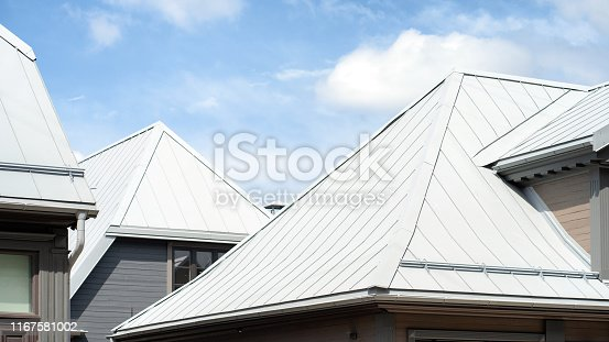 New metal roofs of houses on a hot day under the sky with clouds