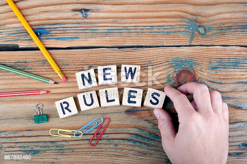 istock new rules. Wooden letters on the office desk 867893460