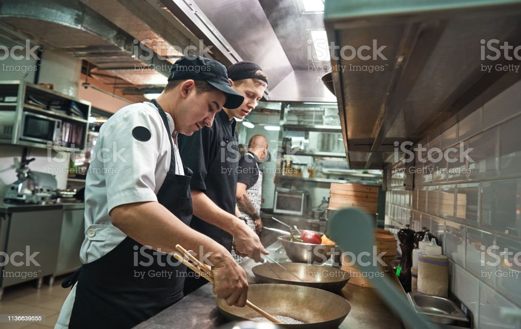 New skills. Two chef assistants cooking a new dish in a restaurant...