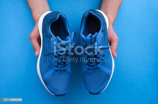 Hands holding a pair of new fitness sport sneakers. Buy a new shoes. Choosing of sneakers for running concept.