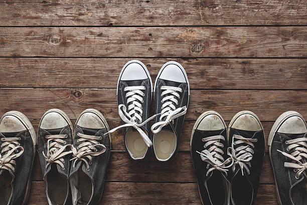 neues sneaker aus segeltuch mit alten schuhe auf hölzerner hintergrund - neue sneaker stock-fotos und bilder