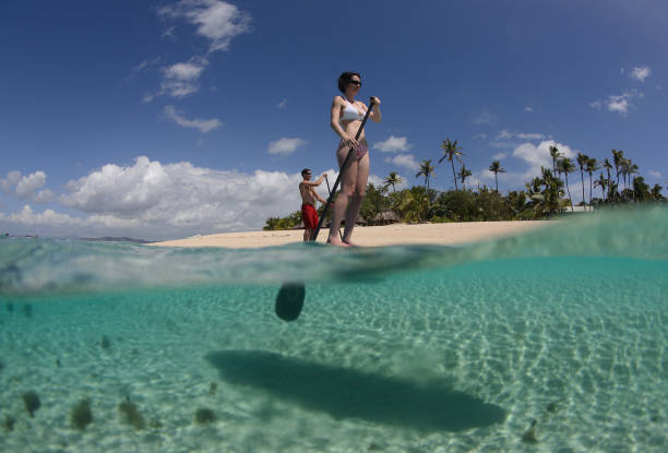 new sports trend  stand-up Paddle boarding a young couple enjoys stand-up paddle boarding in the crystal clear waters of the Fiji Islands south pacific ocean stock pictures, royalty-free photos & images
