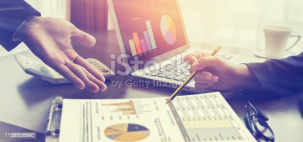 istock New startup business project,Business meeting time,account managers crew working with new startup project,pointing hands,Laptop Notebook on wood table.analyze plans,vintage tone,morning light flare 1138508992