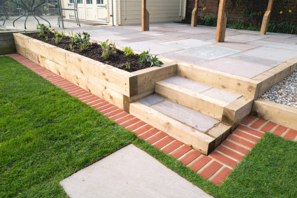 New steps in a garden or back yard leading to a raised patio, alongside a new raised flowerbed made using wooden sleepers. A mowing strip of bricks is in front of newly laid turf. stock photo