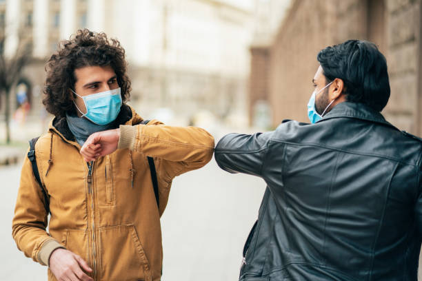 New style greetings in quarantine Young people friends meeting in quarantine and greeting without touching their hands quarantine stock pictures, royalty-free photos & images