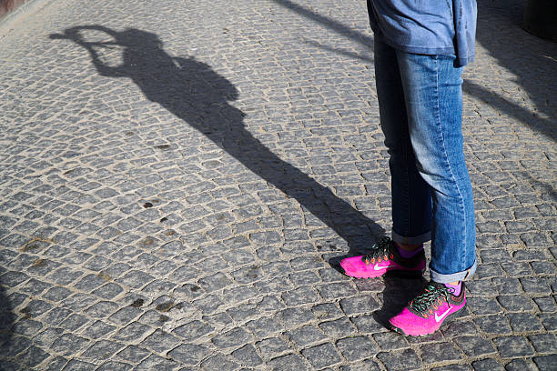 new style pink nike shoes at street with photographers shadow - nike damen sneaker stock-fotos und bilder