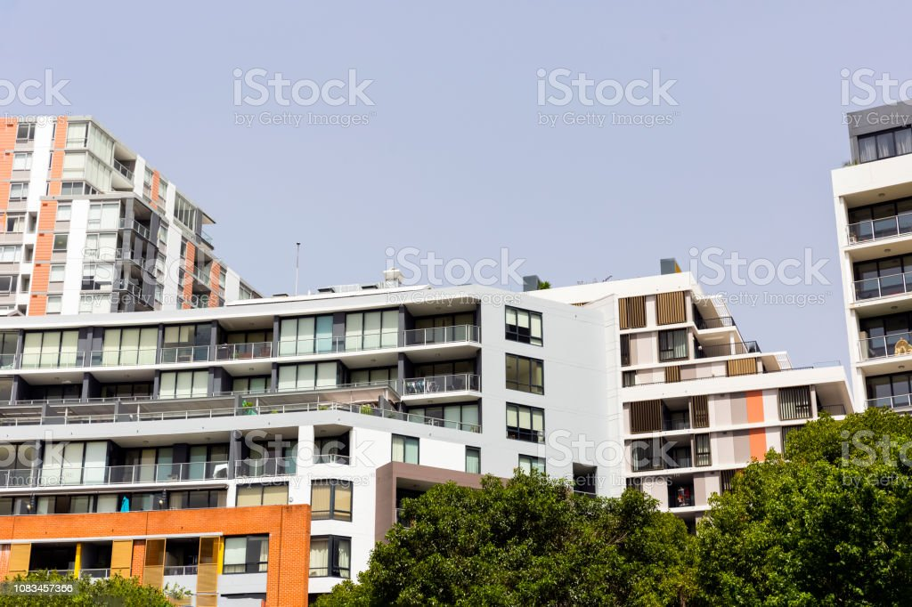 New suburb with apartment buildings, blue sky background with copy...