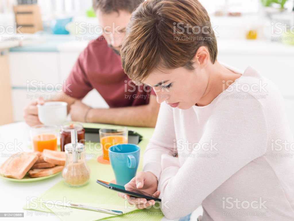 Young couple having breakfast at home, they are using mobile devices,...