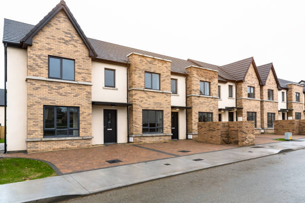New terraced houses for sale in a residential development Newly built row houses for sale in a Residential district ona cloudy winter day housing development stock pictures, royalty-free photos & images