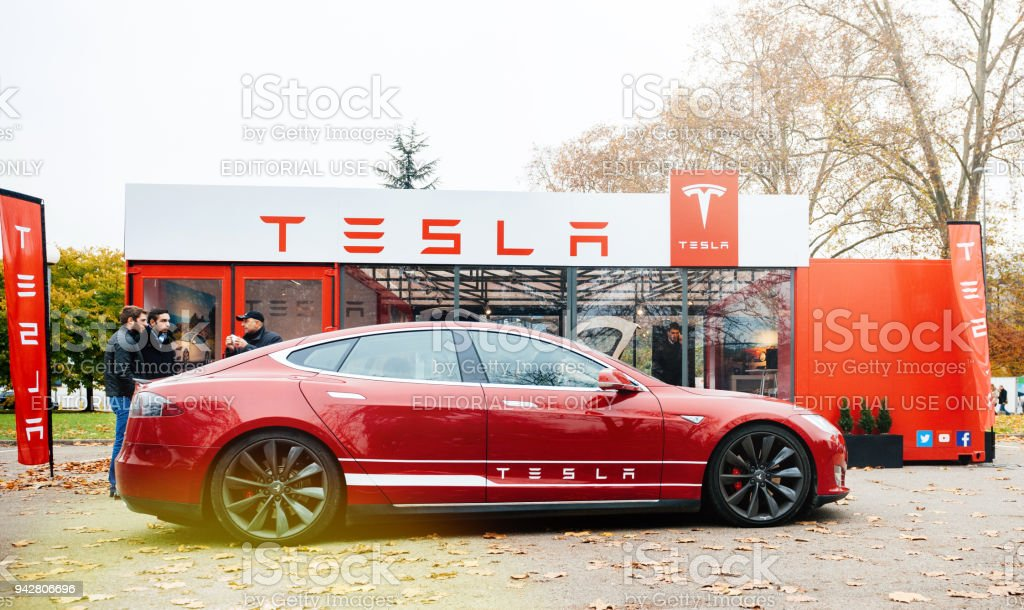 New Tesla Model S showroom parked in front of the red showroom Paris: View from the street of new Tesla Model S showroom parked in front of the showroom with customers admiring the red electric luxury car Alternative Fuel Vehicle Stock Photo