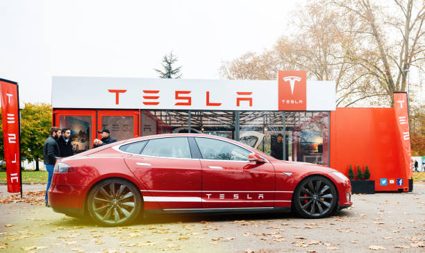 New Tesla Model S showroom parked in front of the red showroom Paris: View from the street of new Tesla Model S showroom parked in front of the showroom with customers admiring the red electric luxury car tesla motors stock pictures, royalty-free photos & images