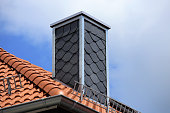 New tiled roof with chimney with slate cladding