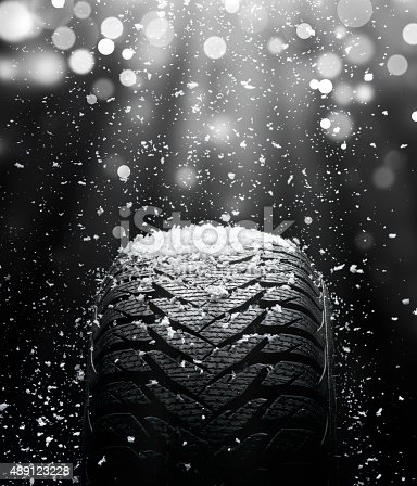 Brand new, wet, high performance wet winter tire Goodyear UltraGrip covered with snow. White beam of light and sparkles above.
