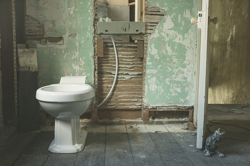 A brand new toilet fitted in an old derelict room being converted to a bathroom