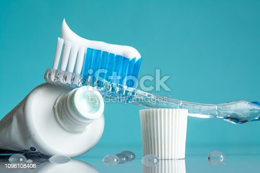 New toothbrush with toothpaste close-up in the bathroom on a mirror table with water drops on a blue background in the sunlight