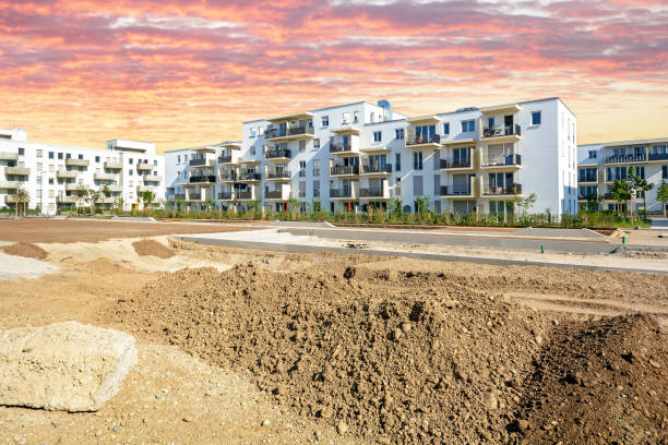 New urban development with construction site and modern residential buildings New urban development with construction site and modern residential buildings grounds stock pictures, royalty-free photos & images