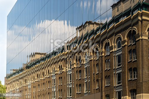 istock New versus old - an old brick building reflected in windows of modern new facade 1060049542