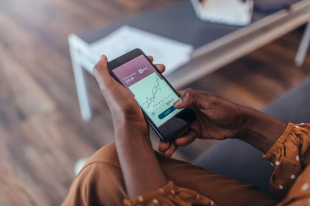 nuovi modi di investire - mani che usano solo lo smartphone - banca foto e immagini stock