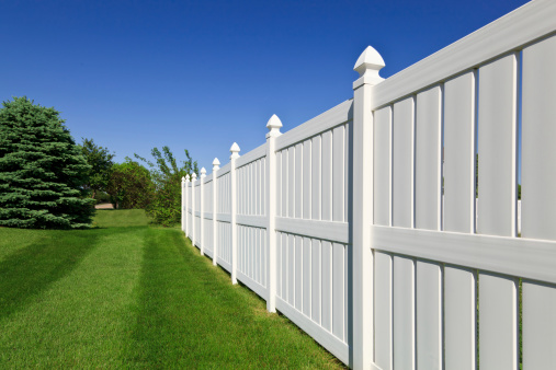 New and contemporary white vinyl fence running across a nicely landscaped backyard with lawn and blue sky in the background.