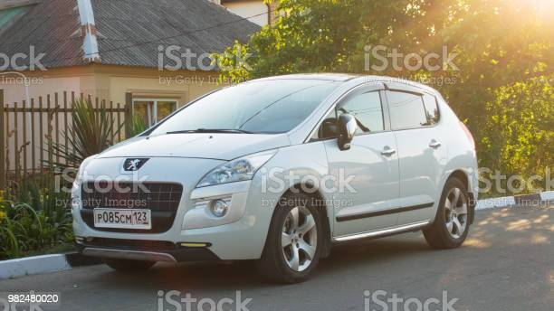 New white Peugeot 2008 parked on suburban road.