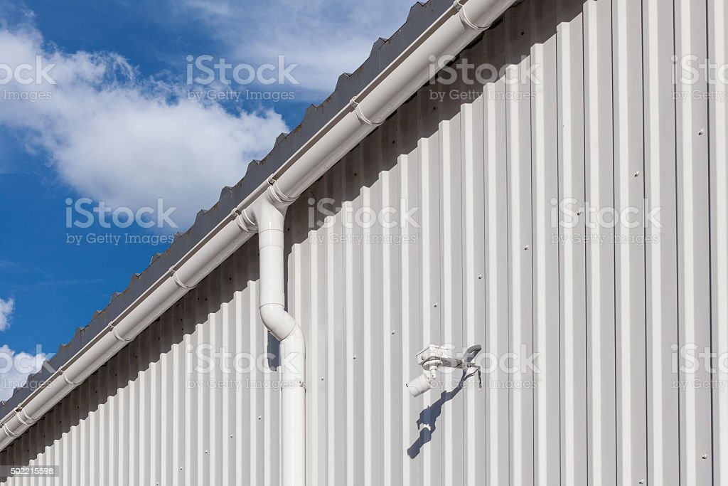 New white rain gutter on building with white metal sheet stock photo