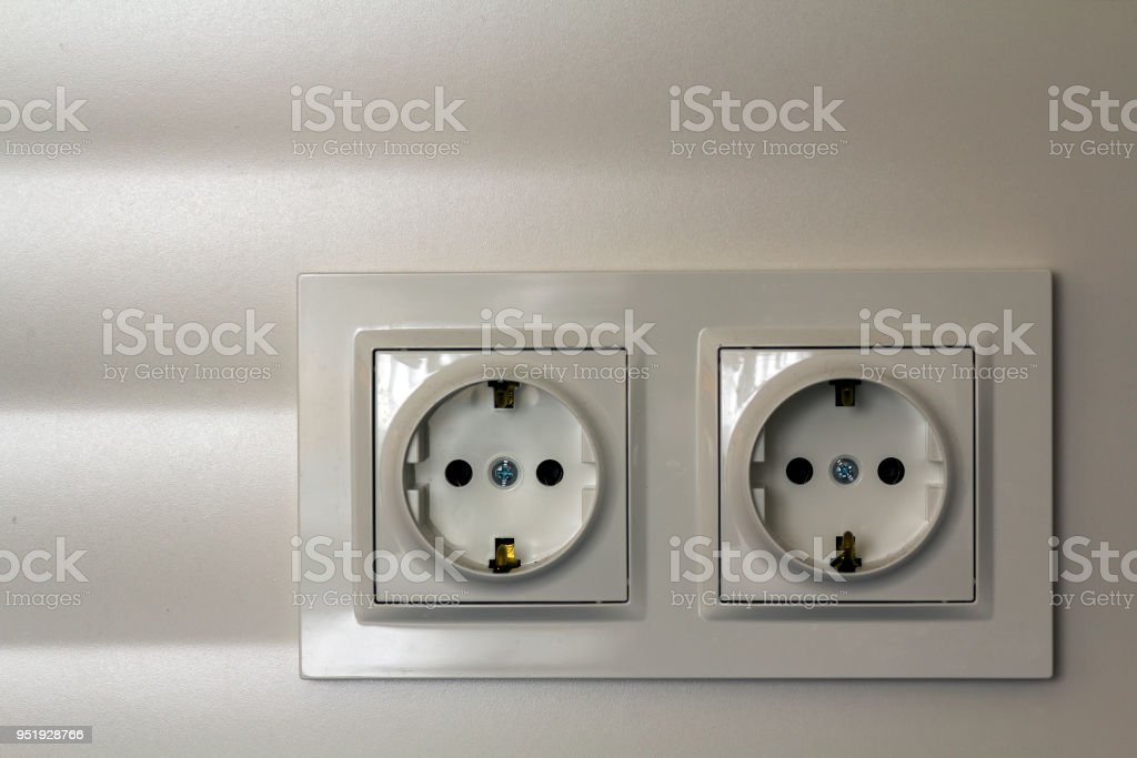 New white shiny plastic electric double sockets on white wall background. Advantages and comfort of modern homes. stock photo