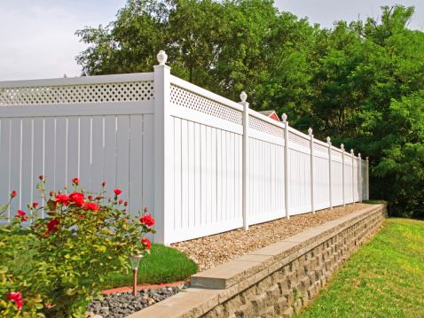 Beautiful white vinyl fence in back yard with nice landscaping in the foreground and background