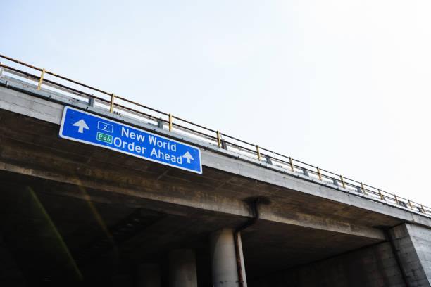 new world order ahead blue road sign against heldere hemel - new world stockfoto's en -beelden