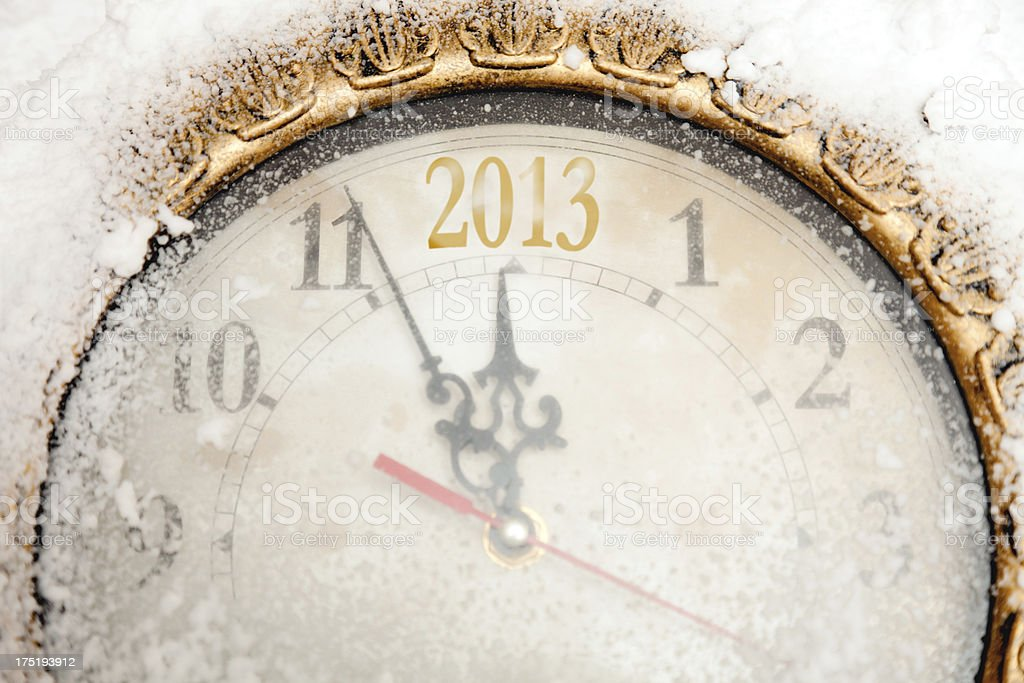 Wall clock covered by snow showing the 2013 New Year countdown.Many...