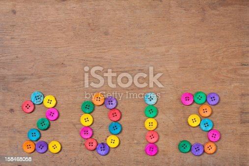 istock New Year 2013 date of color buttons on wooden background 158468058